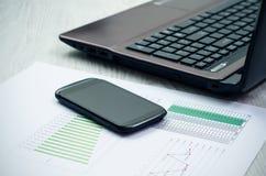 Den moderna bärbara datorn och ilar telefonen på träskrivbordet Arkivbild