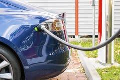 Den moderna elbilen pluggade till uppladdningsstationen i en parkeringsplats Royaltyfri Bild
