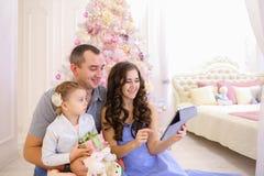 Den moderna familjen talar med släktingar på Skype i rymligt sovrum Royaltyfri Fotografi