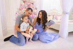 Den moderna familjen talar med släktingar på Skype i rymligt sovrum Royaltyfri Bild
