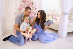 Den moderna familjen talar med släktingar på Skype i rymligt sovrum Royaltyfri Foto