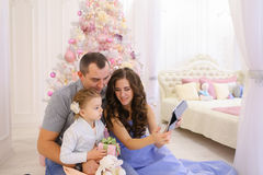Den moderna familjen talar med släktingar på Skype i rymligt sovrum Arkivfoton