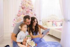 Den moderna familjen talar med släktingar på Skype i rymligt sovrum Arkivfoto