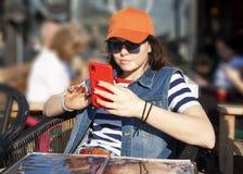 Den moderna flickan skriver ett meddelande på en mobiltelefon arkivfoton