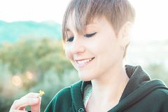 Den moderna flickan som ser en blomma, och en sol piskar i bakgrunden royaltyfri fotografi