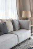 Den moderna gråa soffan med kuddar och den moderna lampan på tabellen sid i l Arkivfoton