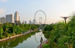 Den moderna gröna staden med tropiskt parkerar och sjön på framdel fotografering för bildbyråer