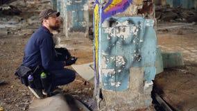 Den moderna grafittimålaren squatting nära kolonn i gamla övergav byggnads- och målninggrafitti med sprutmålningsfärg arkivfilmer