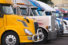 Den moderna gula halva lastbilen på förgrund av annan åker lastbil Fotografering för Bildbyråer