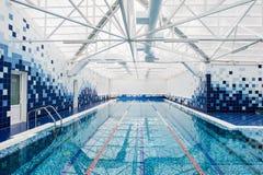 Den moderna inomhus ljusa simbassängen dekorerade med blåa tegelplattor Arkivfoto