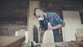 Den moderna inredningssnickaren som rymmer en yxa och, hugger av ett stycke av trä stock video