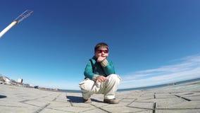 Den moderna kalla pojken sitter utomhus lager videofilmer