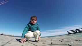 Den moderna kalla pojken sitter utomhus arkivfilmer