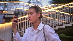 Den moderna kvinnan står på bron, tar fotoet av solnedgången på smartphonen, det stads- begreppet, stege med ljus på bakgrund arkivfilmer