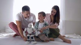 Den moderna leksaker, pysen med modern och fadern spelar den Humanoid roboten på fjärrkontroll av smartphonen som sitter på golv arkivfilmer