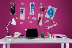 Den moderna märkes- arbetsplatsen med mode skissar och bärbara datorn Royaltyfria Bilder