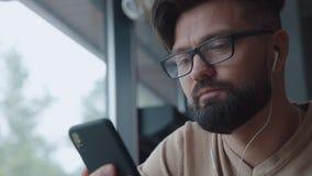 Den moderna mannen talar på videoen, genom att använda smartphonen och hörlurar stock video