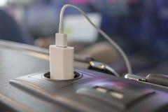 Den moderna mobiltelefonuppladdaren pluggade på den elektriska håligheten i flygplats Arkivbild