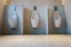 Den moderna och moderna inre av den offentliga toaletten, pissoar bugar Arkivbild