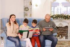 Den moderna och mobila familjen, två söner och maken och frun är upptagna Royaltyfri Foto