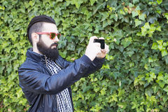 Den moderna och sexiga mannen med skägget tar ett foto Arkivbild