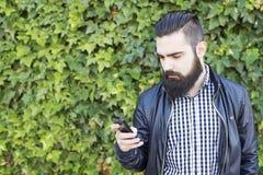 Den moderna och sexiga mannen med skägget tar ett foto Royaltyfri Foto