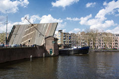 Den moderna pråm på floden under den öppna bron i Amsterdam Arkivbild
