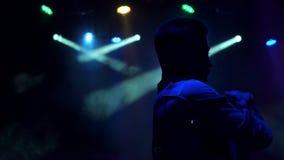 Den moderna unga grabben dansar i mörkret i en nattklubb arkivfilmer