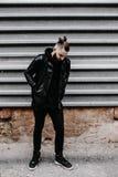 Den moderna unga skäggiga mannen i svart stil beklär anseende in runt om stads- bakgrund Royaltyfri Fotografi