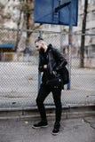 Den moderna unga skäggiga mannen i svart stil beklär anseende in runt om stads- bakgrund Arkivbild