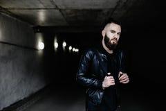 Den moderna unga skäggiga mannen i svart stil beklär anseende in runt om stads- bakgrund Royaltyfri Foto