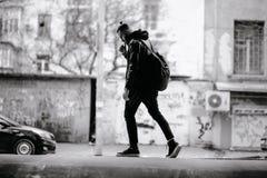 Den moderna unga skäggiga mannen i svart stil beklär anseende in runt om stads- bakgrund Royaltyfri Bild