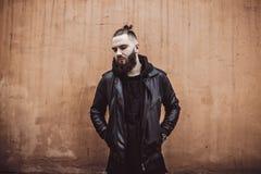 Den moderna unga skäggiga mannen i svart stil beklär anseende in runt om stads- bakgrund Royaltyfria Bilder