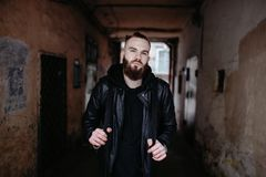 Den moderna unga skäggiga mannen i svart stil beklär anseende in runt om stads- bakgrund Arkivfoton