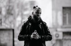 Den moderna unga skäggiga mannen i svart stil beklär anseende in runt om stads- bakgrund Arkivbilder