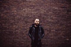 Den moderna unga skäggiga mannen i svart stil beklär att posera mot tegelstenväggen Royaltyfri Fotografi
