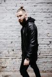 Den moderna unga skäggiga mannen i svart stil beklär att posera mot tegelstenväggen Arkivbilder