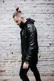 Den moderna unga skäggiga mannen i svart stil beklär att posera mot tegelstenväggen Arkivfoto