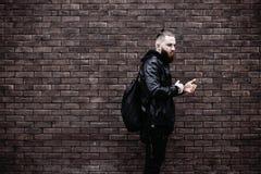 Den moderna unga skäggiga mannen i svart stil beklär att posera mot tegelstenväggen Royaltyfri Foto