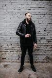 Den moderna unga skäggiga mannen i svart stil beklär att posera mot tegelstenväggen Royaltyfri Bild