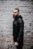 Den moderna unga skäggiga mannen i svart stil beklär att posera mot tegelstenväggen Arkivfoton