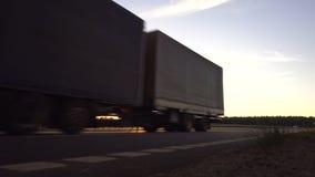 Den moderna vagnlastbilen transporterar last mot bakgrunden av en solnedgång Begreppet av lastbilsförare i fältet av arkivfilmer