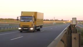Den moderna vagnlastbilen transporterar last mot bakgrunden av en solnedgång Begreppet av lastbilsförare i fältet av lager videofilmer