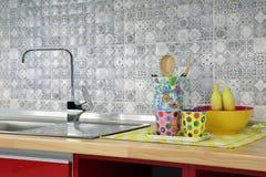 Den moderna vasken med den utsmyckade koppen och redskapet i kök hyr rum Arkivfoto