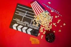 Den moderna yrkesmässiga filmkameran med Mattebox och följer fokusen på abstrakt utrymmebakgrund Clapperboard, biljett och popcor Arkivbilder