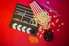 Den moderna yrkesmässiga filmkameran med Mattebox och följer fokusen på abstrakt utrymmebakgrund Clapperboard, biljett och popcor Royaltyfria Bilder