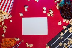 Den moderna yrkesmässiga filmkameran med Mattebox och följer fokusen på abstrakt utrymmebakgrund Clapperboard, biljett och popcor Arkivfoto