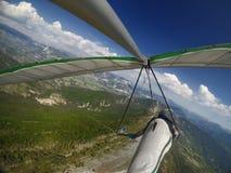 Den modiga extrema hängningglidflygplanpiloten flyger över alpin bergkant Fotografering för Bildbyråer