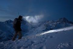 Den modiga nattutforskaren klättrar på höga snöig berg och tänder vägen med en pannlampa Extrem expedition Ski turnerar Snowboard royaltyfria bilder