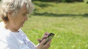 Den mogna äldre kvinnan rymmer en mobiltelefon utomhus lager videofilmer